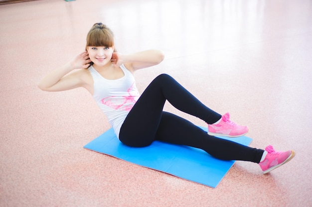 Mujer haciendo ejercicios de estiramiento en el piso en el gimnasio
