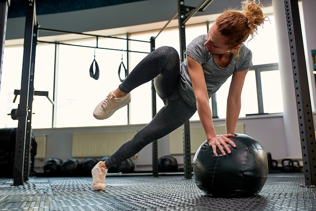 Mujer haciendo ejercicios con fitball en clase de gimnasia de fitness. involucrar los músculos abdominales centrales. concepto de imagen de estilo de vida saludable para las mujeres.