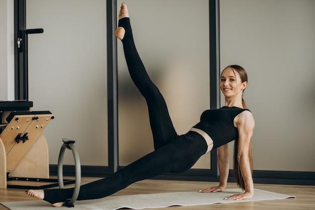 Mujer haciendo ejercicios de pilates en el reformador