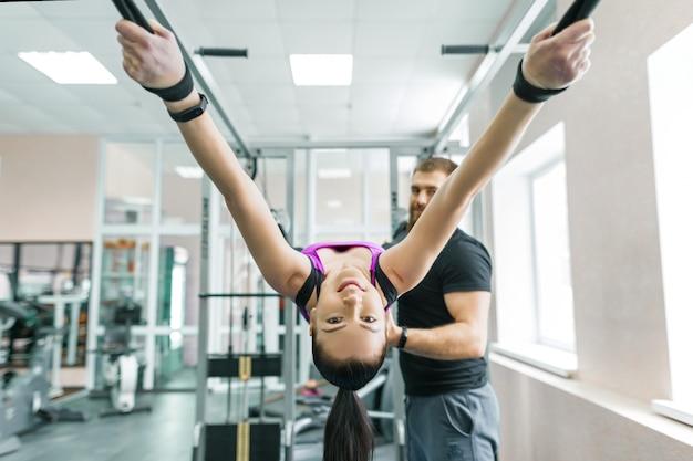 Mujer haciendo ejercicios de rehabilitación con instructor personal