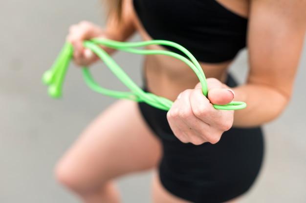 Mujer haciendo ejercicios con la vista cercana de comba