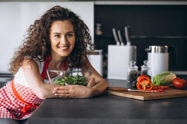 Mujer haciendo ensalada en la cocina