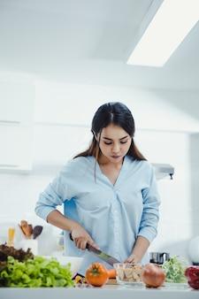 Mujer está haciendo ensalada fresca en la cocina.