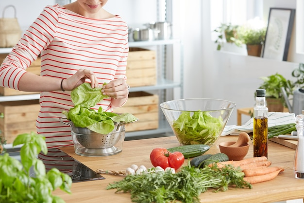 Mujer haciendo ensalada saludable de verduras frescas