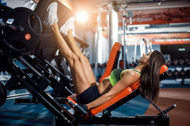 Mujer haciendo entrenamiento físico en una máquina de empuje de extensión de pierna con pesas
