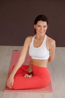 Mujer haciendo estiramientos sobre la estera en el estudio. día de yoga felicidad y meditación