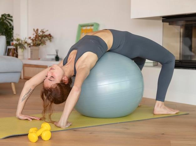 Mujer haciendo fitness en casa en bola