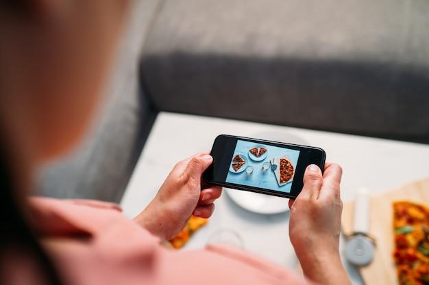 Mujer haciendo una foto con el teléfono inteligente de una pizza italiana casera en la mesa de la sala