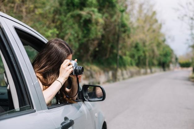 Mujer haciendo una foto por ventana de coche
