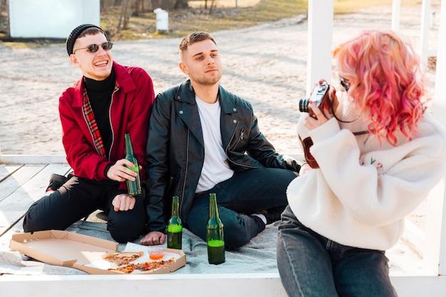 Mujer haciendo fotos de sonriente pareja de hombre en picnic