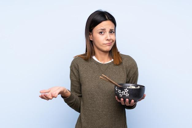 Mujer haciendo gesto de dudas mientras levanta los hombros mientras sostiene un tazón de fideos con palillos