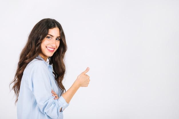 Mujer haciendo gesto de pulgar arriba hacia copyspace