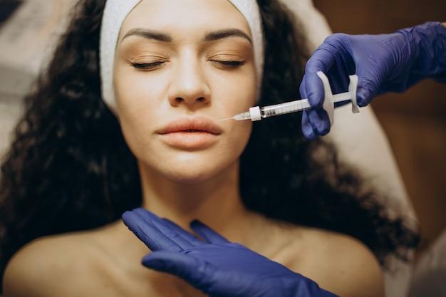 Mujer haciendo inyecciones en cosmetóloga
