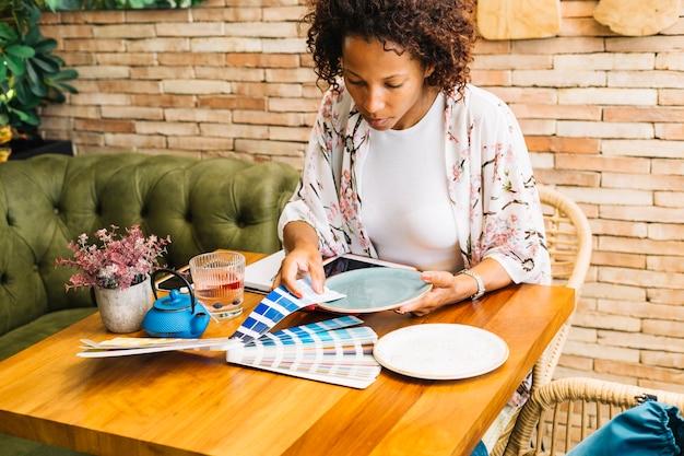 Mujer haciendo juego con la muestra de color con plato en la mesa