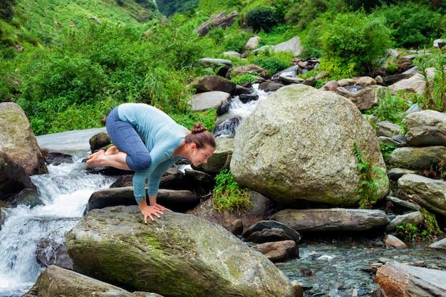 Mujer haciendo kakasana asana equilibrio del brazo al aire libre
