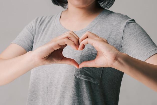 Mujer haciendo manos en forma de corazón, donación, voluntario de caridad feliz, concepto del día mundial del corazón