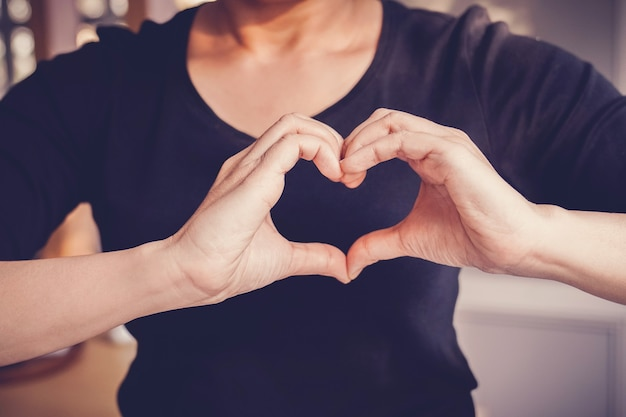 Mujer haciendo las manos en señal de forma de corazón, día mundial del corazón