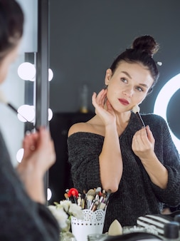 Mujer haciendo maquillaje tiro medio