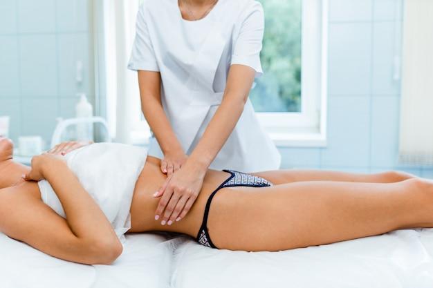 Mujer haciendo un masaje de vientre en la sala de procedimientos de luz. masaje anticelulítico, diástasis.