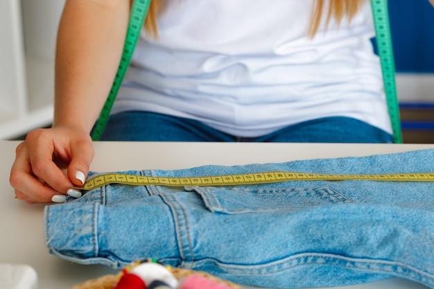 Mujer haciendo medidas a medida con cinta métrica en su oficina