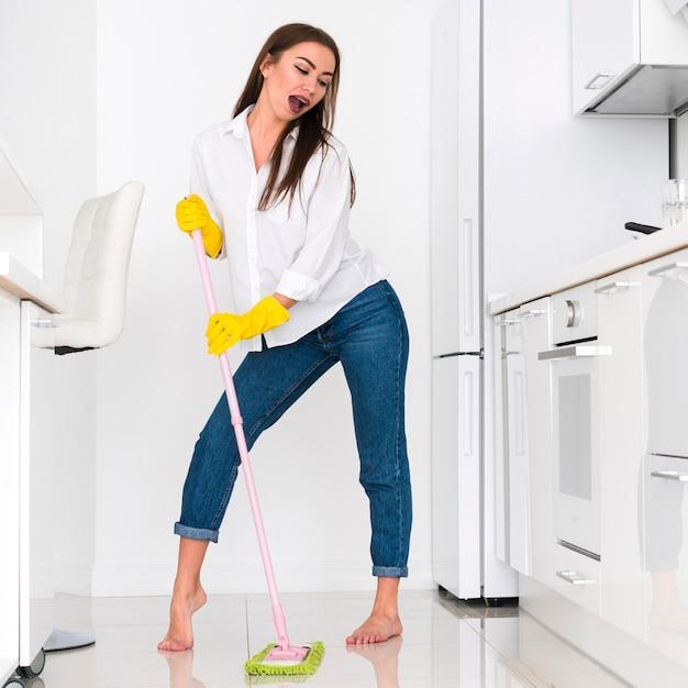 Mujer haciendo muecas mientras limpia