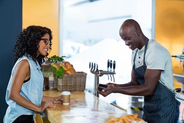 Mujer haciendo el pago con tarjeta de crédito en el mostrador