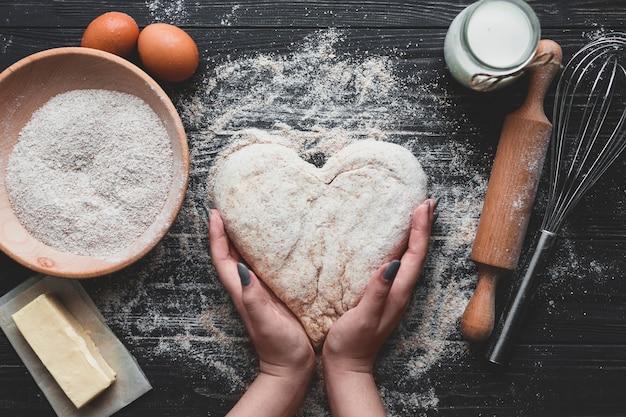 Mujer haciendo pan en forma de corazón
