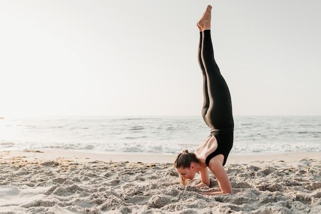 Mujer haciendo parada de manos en la arena cerca del océano practicando yoga asanas