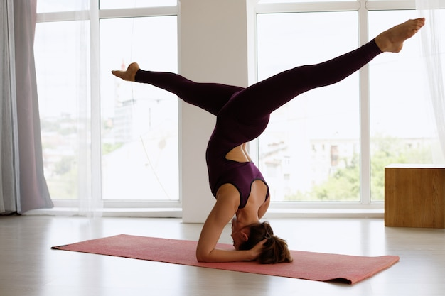 Mujer haciendo parada de manos en el día de yoga