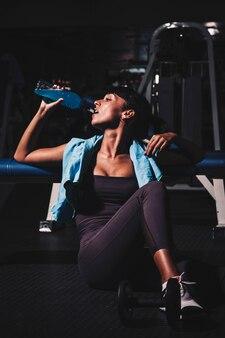 Mujer haciendo una pausa en gimnasio
