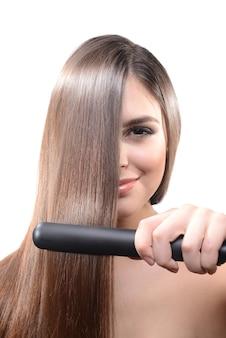Mujer haciendo peinado con plancha de pelo en blanco
