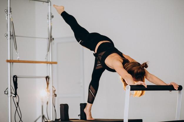 Mujer haciendo pilates en un reformador
