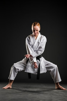 Mujer haciendo pose de karate tiro completo