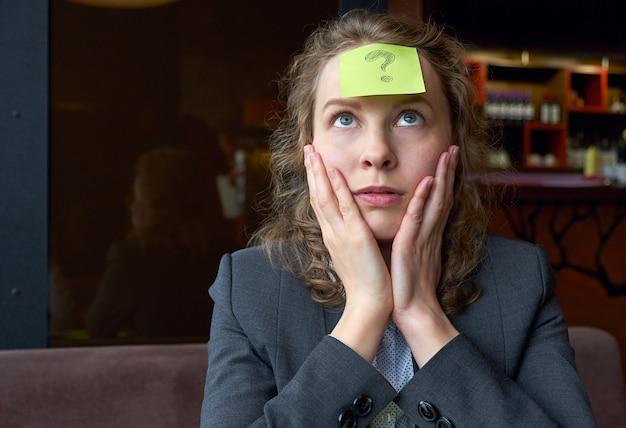 Mujer haciendo preguntas pegatina en la frente. búsqueda de retrato conceptual para una respuesta a una pregunta