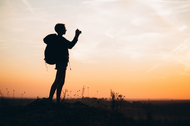 Mujer haciendo senderismo en las montañas y haciendo fotos.