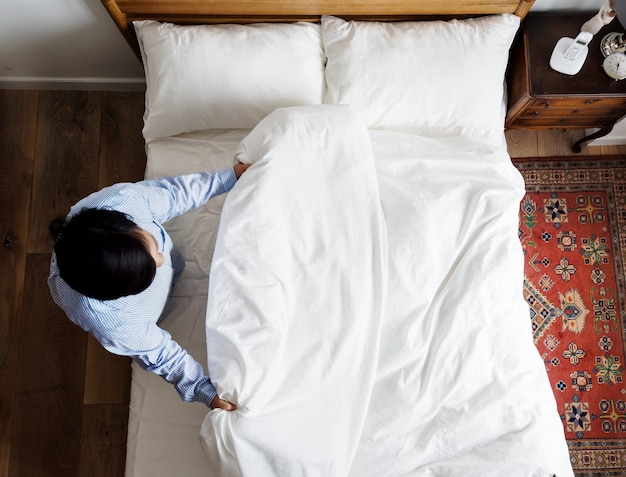 Mujer haciendo su cama en la mañana