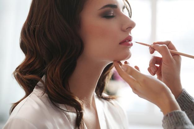 Mujer haciendo su maquillaje hecho por un maquillador