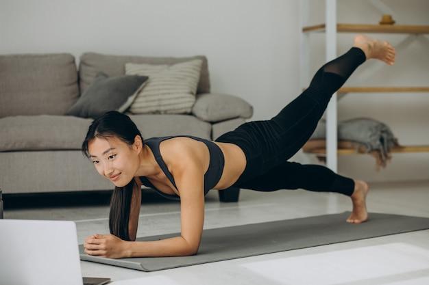 Mujer haciendo tabla de yoga en casa en mat