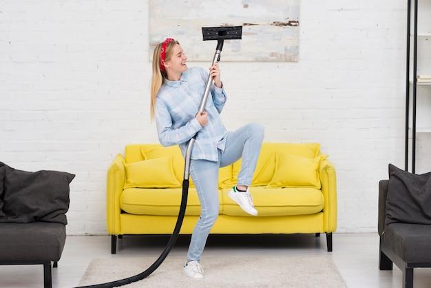 Mujer haciendo tareas domésticas con vacío