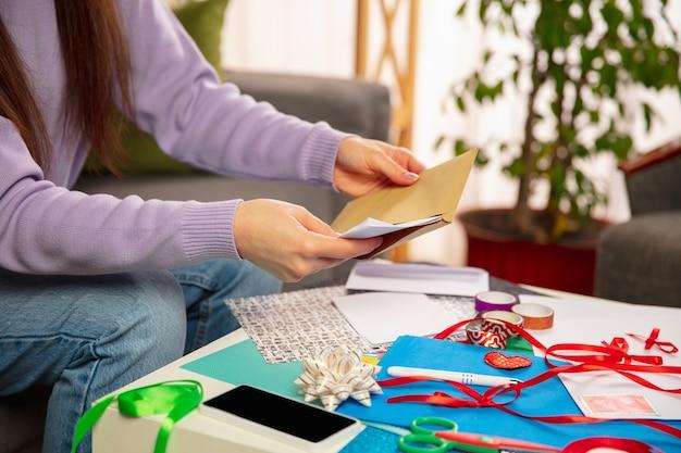 Mujer haciendo tarjetas de felicitación para año nuevo y navidad 2021 para amigos o familiares, reserva de chatarra, bricolaje
