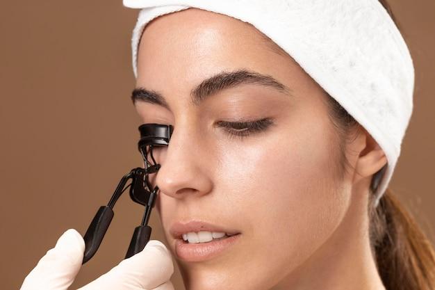 Mujer haciendo un tratamiento de pestañas a su cliente