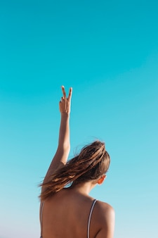 Mujer haciendo v suspiro en el cielo