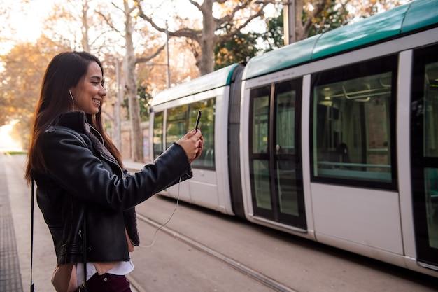 Mujer haciendo videollamada con teléfono en la calle