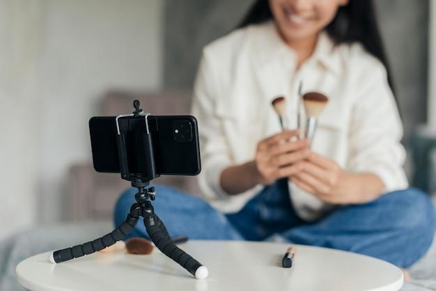 Mujer haciendo un vlog sobre maquillaje en interiores