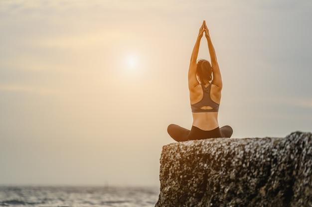 Una mujer haciendo yoga asana sentada en la piedra en el mar. entrenamiento de calentamiento de estiramiento natural matutino. concepto de yoga, fitness y estilo de vida saludable.