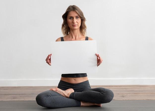 Mujer haciendo yoga en casa y sosteniendo un cartel en blanco