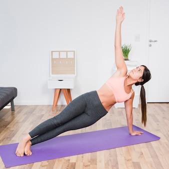 Mujer haciendo yoga en casa