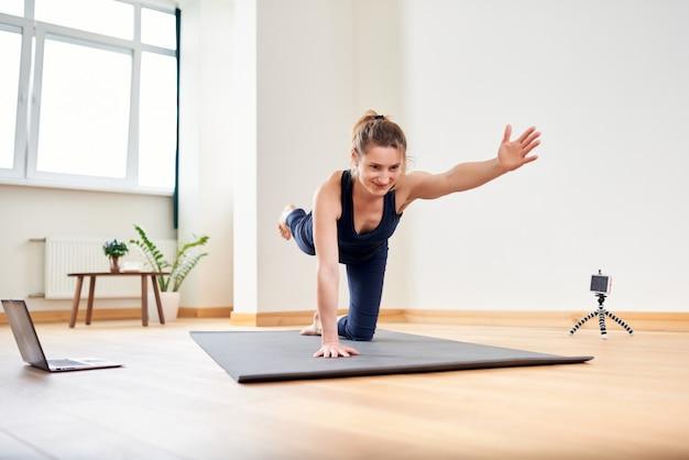 Mujer haciendo yoga en línea. computadora y cámara en su sala de estar. estilo de vida saludable y conceptos de trabajo a distancia.