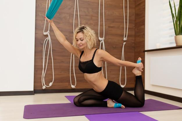 Mujer haciendo yoga mosca estirando ejercicios en el gimnasio. estilo de vida en forma y bienestar