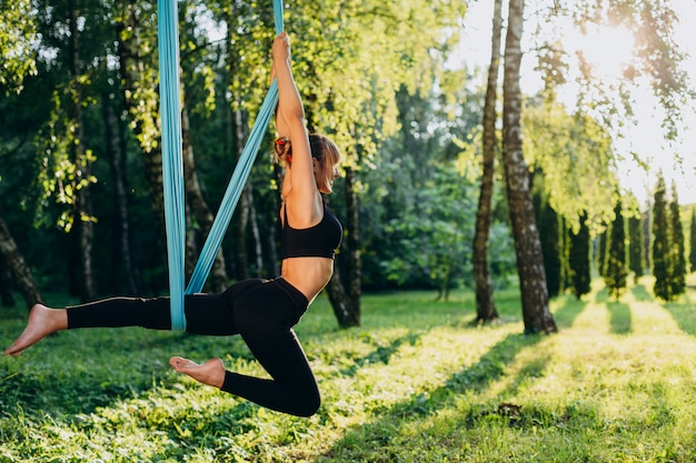 Mujer haciendo yoga mosca en el parque al aire libre. vista lateral